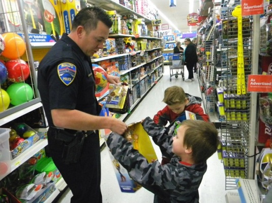 Rialto police Cpl. Cameron Nelson shops for Christmas presents with brothers Nicholas and Kristian Mingl for the Police Department's second annual Shop With a Cop event. Nicholas might have been disappointed that he didn't get a sleigh ride but he did get a much brighter holiday. (Melissa Pinion-Whitt Staff)