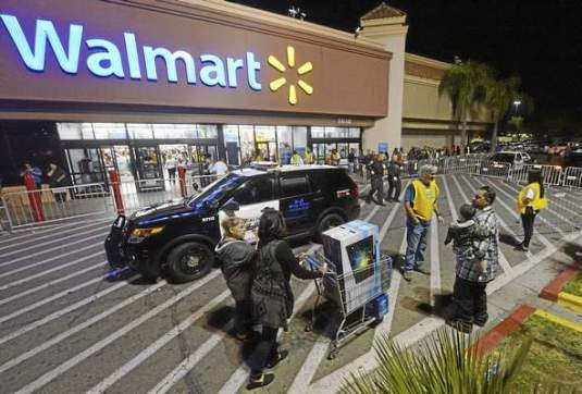 Rialto police vehicles sit outside the Rialto Walmart Thursday night after fights occurred at the store. Police said there were three fights shortly after 7 p.m. at the store at 1610 S. Riverside Ave., two of which were inside over merchandise and the third outside that caused injury to an officer. Will Lester – Staff Photographer