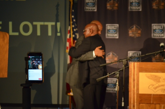 Ronnie Lott and father Roy Lott hug before reveling the Hall of Famer trophy